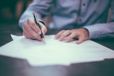 紙にペンで書く人